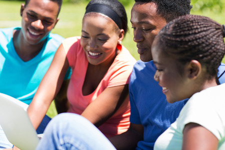 young african american woman: group of college students using laptop computer outdoors on campus