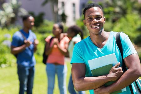 estudiantes adultos: felices del estudiante universitario africano celebraci�n de los libros masculinos Foto de archivo