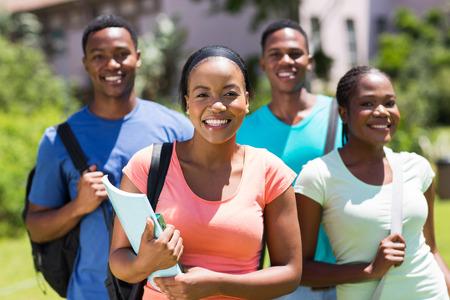 estudiantes adultos: hermosa chica universitaria estadounidense de pie delante de los amigos Foto de archivo