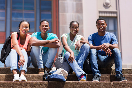 african lady: group of happy african student sitting outside college building