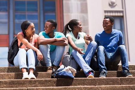 estudiantes adultos: grupo de amigos de la universidad afroamericanos lindos que se sientan en las escaleras