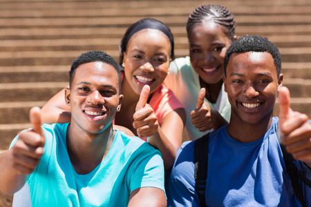 estudiantes adultos: grupo de alegres amigos africanos dando pulgar hacia arriba Foto de archivo