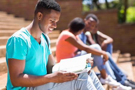estudiantes adultos: inteligente africano estudiante universitaria americana de leer un libro al aire libre