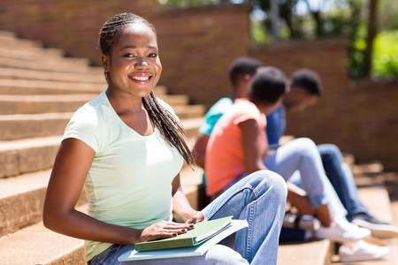 portrait of african college girl sitting on steps photo