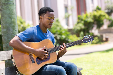 young african college student playing guitar outdoors photo