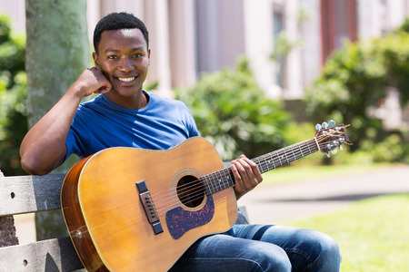 portrait of handsome african college student with a guitar outdoors photo
