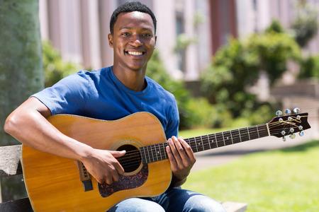 guitarra: alegre joven African American hombre que toca la guitarra al aire libre Foto de archivo