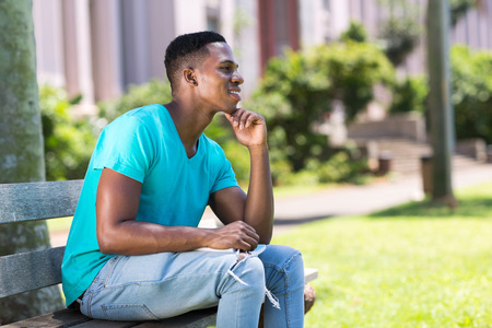 daydreaming: handsome african college student daydreaming