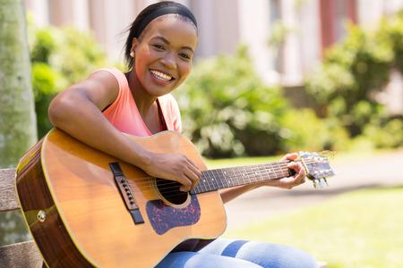 playing music: beautiful african american woman playing guitar outdoors