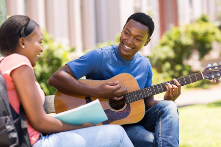 a guitarist boy playing guitar: romantic young african college student playing guitar for his girlfriend on campus