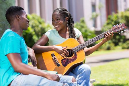 beautiful african girl playing guitar for her boyfriend photo