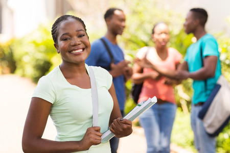 african student: cheerful female african american university student holding books on campus