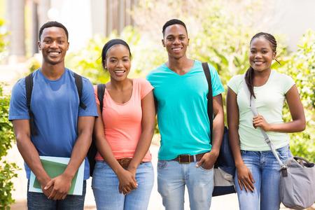 estudiantes adultos: grupo de estudiantes universitarios africano feliz de pie juntos en el campus