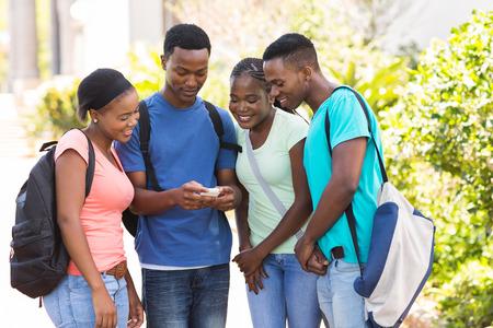 estudiantes adultos: grupo de estudiantes universitarios afroamericano lindo que usa el tel�fono celular en el campus
