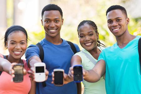 adult learners: estudiantes universitarios africanos de grupo que muestran los teléfonos inteligentes