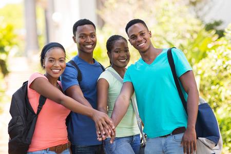 adult learners: grupo de alegres estudiantes universitarios africanos ponen las manos juntas Foto de archivo