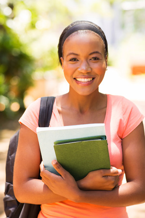 beautiful african university student holding books photo