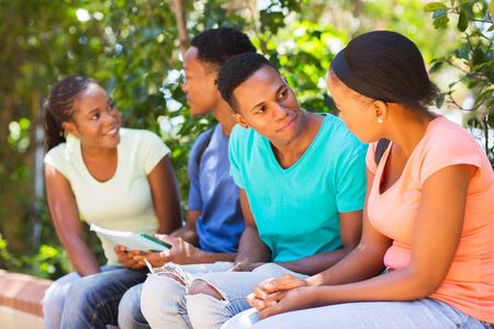 estudiantes adultos: grupo de jóvenes estudiantes universitarios que se sientan al aire libre