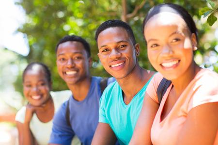 adult learners: grupo de estudiantes universitarios africanos sentados al aire libre
