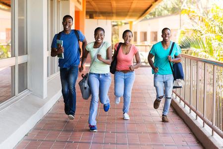 estudiantes adultos: alegres estudiantes universitarios africanos corriendo a dar una conferencia pasillo