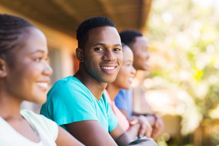 estudiantes adultos: buen chico africano Colegio Americano de aspecto con un grupo de amigos