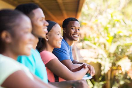 estudiantes adultos: alegre muchacho joven universitario africano con sus amigos en el campus