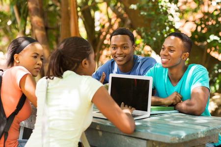 gruppo di studenti che utilizzano computer portatile su campus universitario Archivio Fotografico