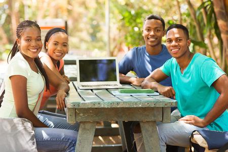 estudiantes adultos: grupo de amigos universitarios africanos sentados juntos al aire libre