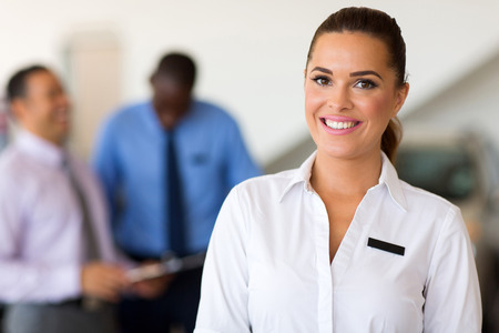 beautiful caucasian saleswoman standing at car dealership