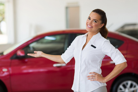 welcome smile: happy young saleswoman welcoming gesture in car showroom Stock Photo