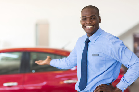 new employee: african car salesman standing at showroom presenting new cars