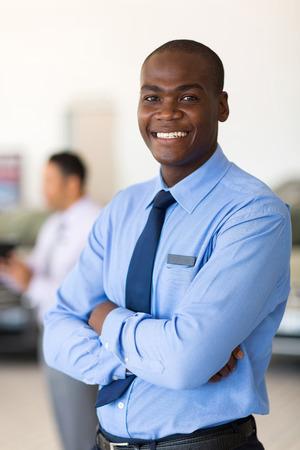 auto sales: portrait of african vehicle salesman in showroom Stock Photo