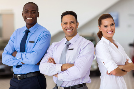 car sales staff standing inside showroom 스톡 콘텐츠