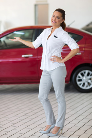 saleswoman: beautiful saleswoman presenting new car to clients Stock Photo