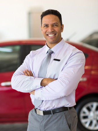 happy male car dealer principal inside showroom Banco de Imagens