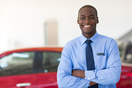 handsome african man working at car dealership Stock Photo