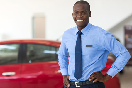 ethnic attire: african american vehicle sales consultant inside showroom Stock Photo