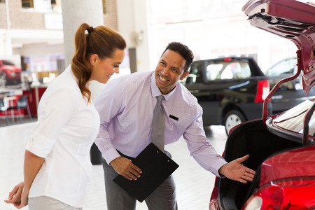 handsome car salesman showing new vehicle to customer