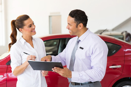 friendly mid age mid age car salesman just made a sale to young customer