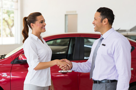 cheerful middle aged car dealer handshake with customer in showroom Archivio Fotografico