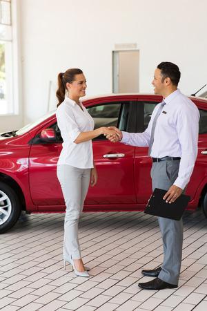 handshaking: attractive young woman handshaking with car salesman in showroom