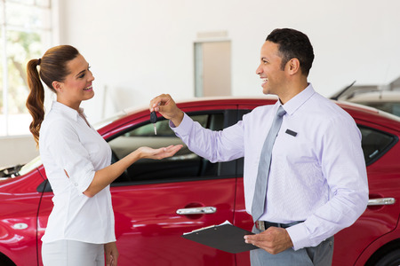 pretty young woman receiving car key from dealership Stockfoto