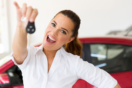 automobile dealership: excited woman holding new car key at vehicle dealership
