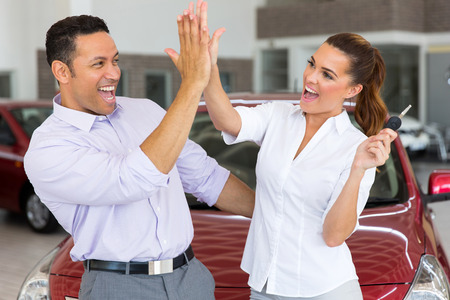 excited mid age couple giving high five after buying new car
