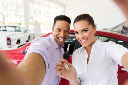 happy customer: happy couple taking selfie together at dealership after bought new car Stock Photo