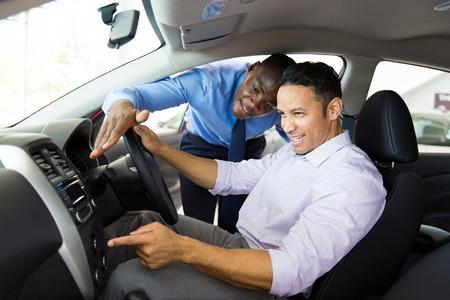 車の中に座っている顧客へのアフリカの車セールスマン示す新しい車内 写真素材
