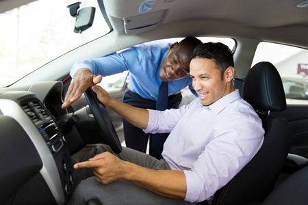 african car salesman showing new car interior to customer sitting inside the car Фото со стока
