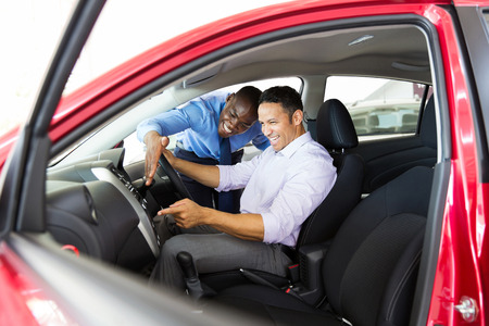 auto sales: happy middle aged man checking car features in showroom