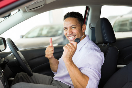 new age: cheerful mid age man giving thumb up inside his new car