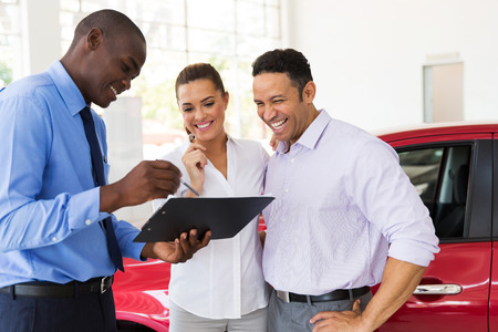 african car dealer explaining sales contract to couple buying a car 스톡 콘텐츠